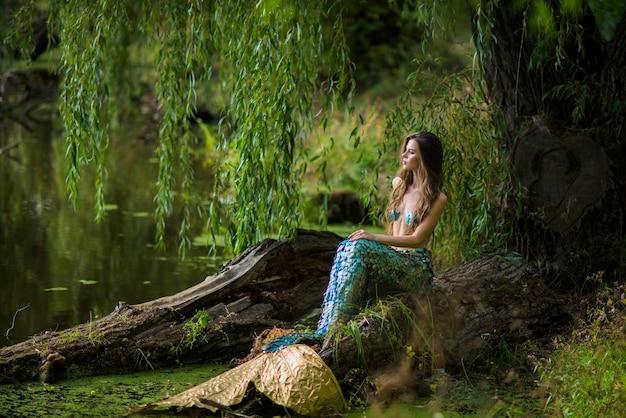Frau mit langen braunen haaren und gekleidet wie eine meerjungfrau sitzt auf dem stein über wasser