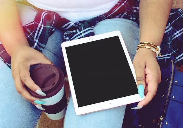 Frau mit langen bunten nägeln, die eine tasse kaffee und eine tablette halten