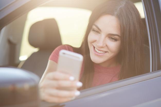 Frau mit langen dunklen haaren, glücklich, nachricht auf smartphone zu erhalten, posiert im auto, hält auf der straße an