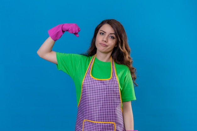 Frau mit langen gewellten haaren, die schürze und gummihandschuhe trägt und bizeps zeigt, der stärke und kraft zeigt, die mit sicherem blick auf blau stehen