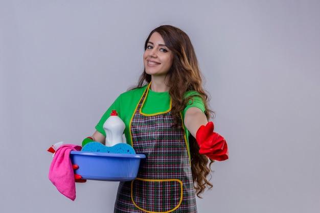 Frau mit langen gewellten haaren, die schürze und gummihandschuhe tragen, die mit becken voller reinigungswerkzeuge stehen, die daumen hoch lächelnd freundlich zeigen erfolg zeigen