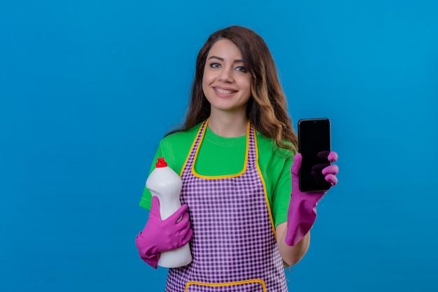 Frau mit langen gewellten haaren, die schürze und gummihandschuhe tragen, die reinigungsmittel halten, das handy lächelnd freundlich stehend auf blau zeigt