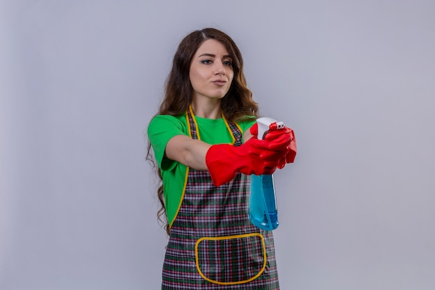 Frau mit langen gewellten haaren, die schürze und gummihandschuhe tragen, die reinigungsspray halten, das wie eine waffe verwendet, die mit sicherem blick steht