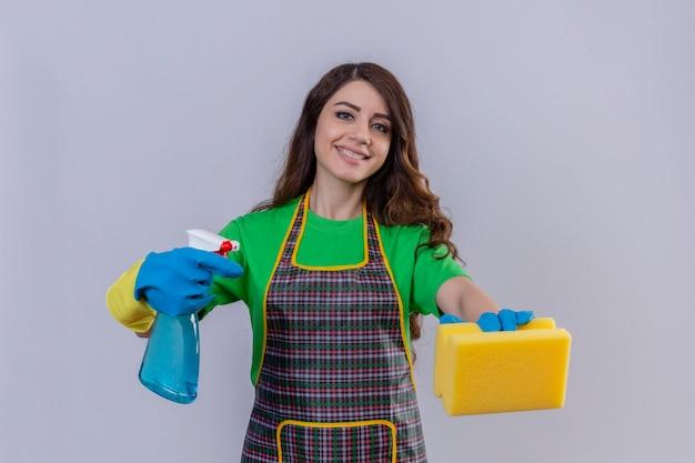 Frau mit langen gewellten haaren, die schürze und gummihandschuhe tragen, die schwamm und reinigungsspray halten, die selbstbewusst und positiv lächelnd bereit sind, stehend zu reinigen