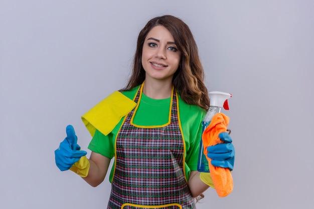 Frau mit langen gewellten haaren, die schürze und gummihandschuhe tragen, die teppich und reinigungsspray halten, die selbstbewusst und positiv lächelnd zeigen und daumen hoch zeigen, die bereit sind, auf blau stehend zu reinigen