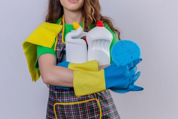 Frau mit langen gewellten haaren, die schürze und gummihandschuhe tragen, die teppich und schwamm der reinigungsmittel in den händen halten, die stehen und lächeln