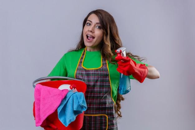 Frau mit langen gewellten haaren, die schürze und gummihandschuhe tragen, eimer mit reinigungswerkzeugen und reinigungsspray haltend freudig lächelnd fröhlich stehend
