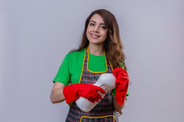 Frau mit langen gewellten haaren, die schürze und gummihandschuhe tragen flasche der reinigungsmittel halten, die positiv und glücklich stehen und lächeln