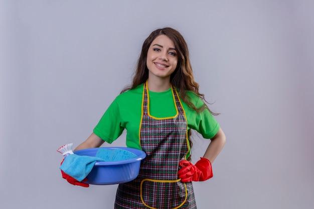 Frau mit langen gewellten haaren, die schürze und gummihandschuhe tragen und mit einem becken voller reinigungswerkzeuge stehen, die selbstbewusst mit glücklichem gesicht selbstzufrieden lächeln
