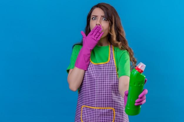 Frau mit langen gewellten haaren, die schürze und gummihandschuhe tragen und mit flasche reinigungsmittel halten, überrascht mit handkegelmund, der auf blau steht