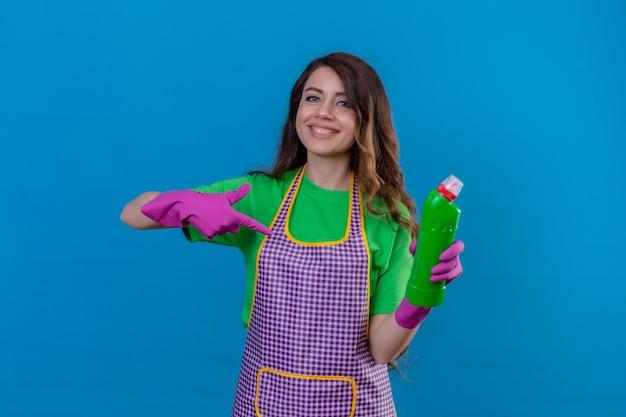 Frau mit langen gewellten haaren, die schürze und gummihandschuhe tragen, zeigt auf flasche mit reinigungsmittel in ihrer hand lächelnd freundlich stehend auf blau