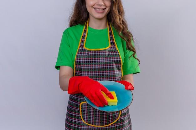 Frau mit langen gewellten haaren, die schürze und gummihandschuhe waschplatte tragen
