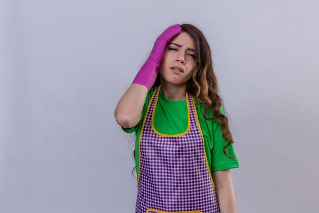 Frau mit langen gewellten haaren in schürze und handschuhen, die müde stehen und mit der hand auf dem kopf stehen und müdigkeit fühlen