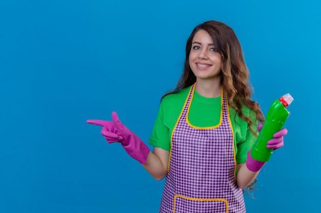 Frau mit langen gewellten haaren in schürze und handschuhen, die reinigungsmittel halten, das zur seite zeigt, die fröhlich auf blau stehend lächelt