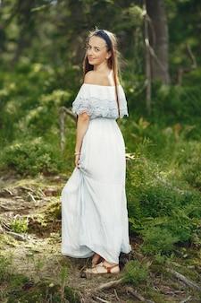 Frau mit langen haaren. dame in einem blauen kleid. mädchen mit unberührter natur.