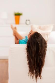 Frau mit langen haaren, die auf der couch entspannen