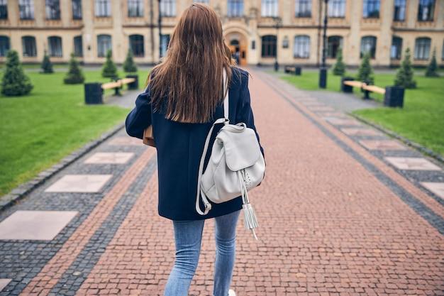 Frau mit langen haaren, die ordner in den händen hält und rucksack alleine zur universität geht