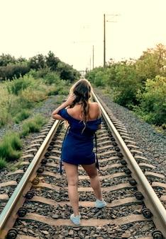Frau mit langen haaren im blauen kleid auf der rückansicht der alten eisenbahn rail