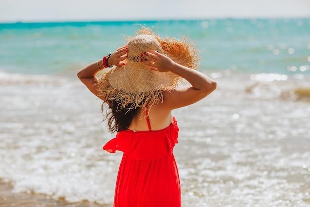 Frau mit langen haaren im roten sommerkleid mit strohhut posiert an der küste.