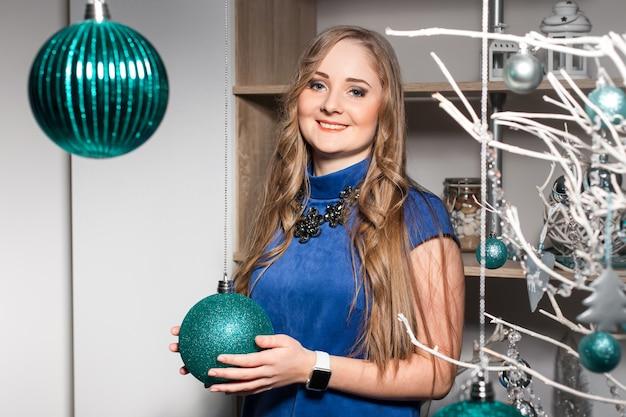 Frau mit langen haaren lächelt gegen weihnachtsschmuck