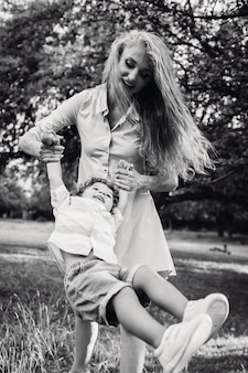 Frau mit langen haaren schwingt ihren sohn im park