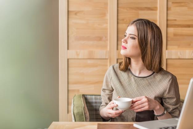 Frau mit langen haaren und eine tasse in den händen