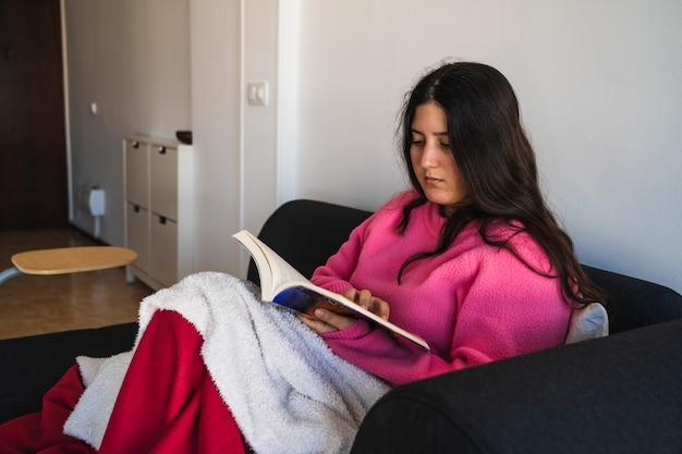 Frau mit langen haaren und einem rosa pullover, der in einem sofa sitzt