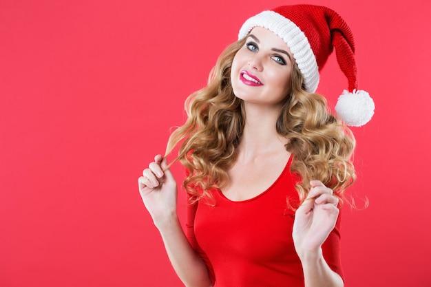 Frau mit langen lockigen haaren und make-up in einer weihnachtsmütze. schönheit, mode und feier.