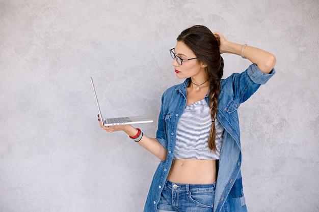 Frau mit laptop berührt haar mit der hand