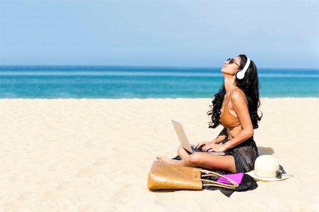 Frau mit laptop-computer am strand