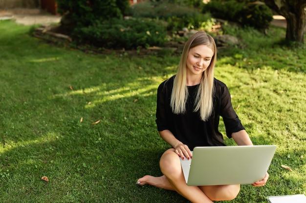 Frau mit laptop, der draußen arbeitet oder lernt.