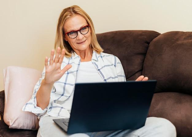 Frau mit laptop, der zu hause während der quarantäne arbeitet
