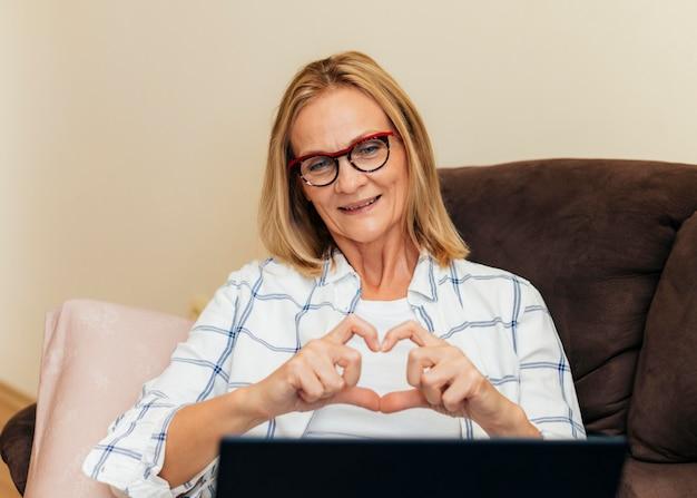 Frau mit laptop, der zu hause während der selbstisolierung arbeitet