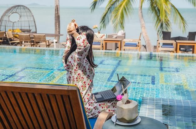 Frau mit laptop, die ihre arme über den kopf streckt und auf das meer blickt Premium Fotos