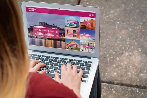 Frau mit laptop ein hotel auf der website buchen