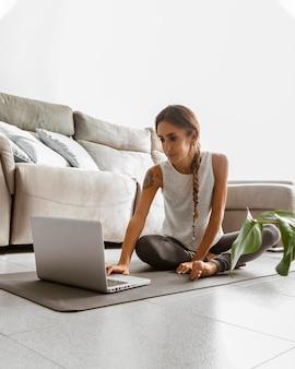 Frau mit laptop macht yoga zu hause