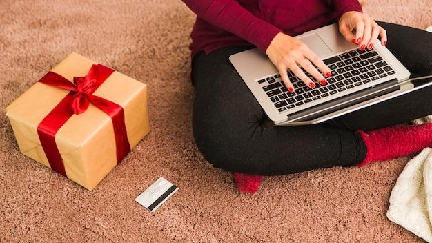 Frau mit laptop nahe plastikkarte und geschenkbox