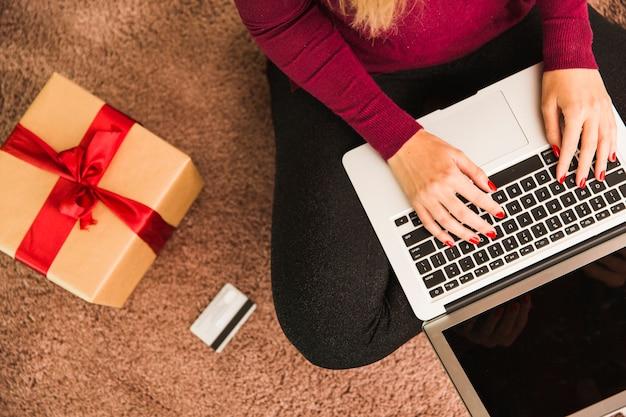 Frau mit laptop nahe plastikkarte und präsentkarton