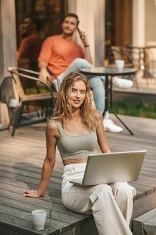 Frau mit laptop sitzt draußen in der nähe von haus und mann