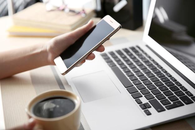 Frau mit laptop und handy zu hause