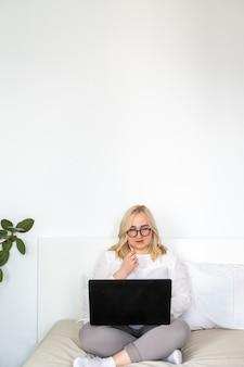 Frau mit laptop und headset zu hause