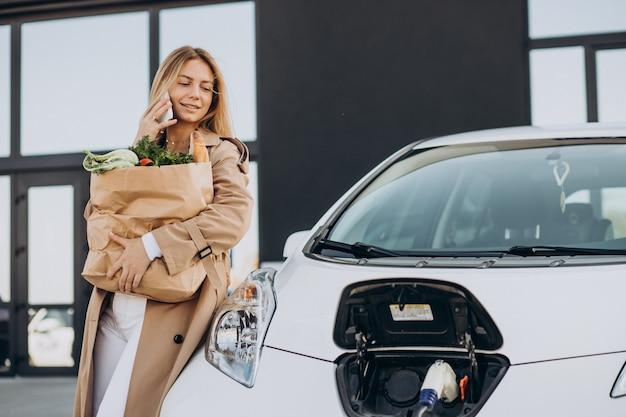 Frau mit lebensmitteleinkaufstaschen, die elektroauto aufladen