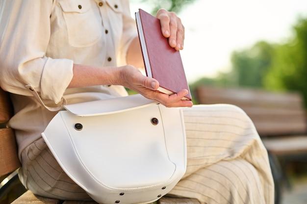 Frau mit ledernotizbuch neben handtasche