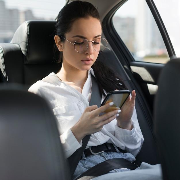 Frau mit lesebrille unter verwendung des telefons