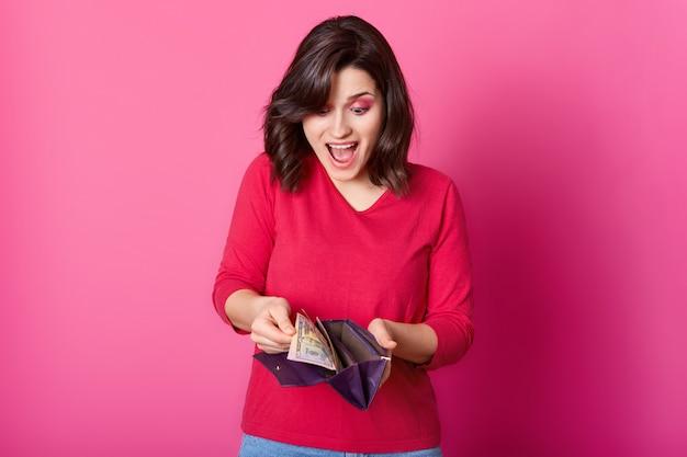 Frau mit lila brieftasche voller geld in den händen sieht erstaunt aus. überraschte frau trägt hemd, hält geöffnete geldbörse