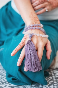Frau mit lila mala perlen auf ihren händen henna mehendi
