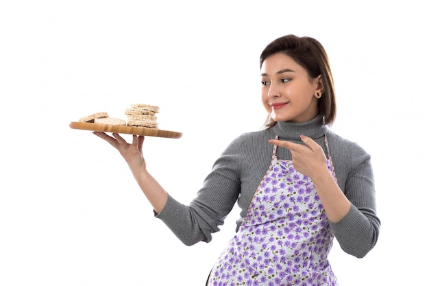 Frau mit lila schürze, die kekse hält