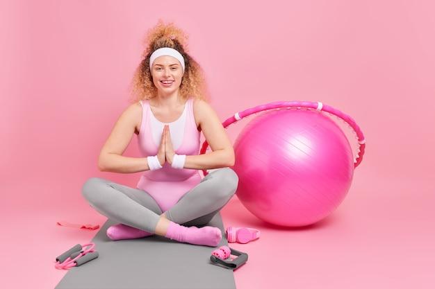 Frau mit lockigem haar hält handflächen zusammengepresst beine gekreuzt praktiziert yoga hat fitnesstraining umgeben von sportgeräten macht sportübungen zu hause. aktiver lebensstil