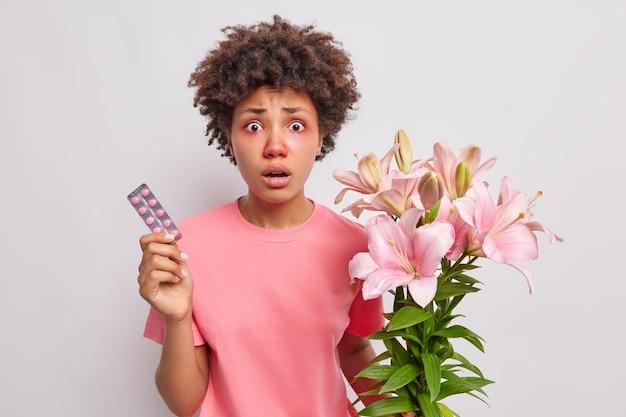 Frau mit lockigem haar hält lilienblumenstrauß hat allergische reaktion auf pollen hält medikamente zur heilung von krankheitssymptomen trägt rosa t-shirt isoliert auf weiß