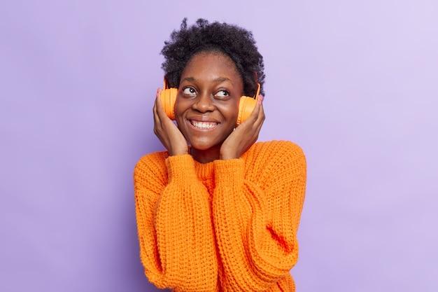 Frau mit lockigem haar hört gerne audiospur hält die hände auf kopfhörer denkt über etwas gutes nach trägt gestrickten orangefarbenen pullover isoliert auf lila